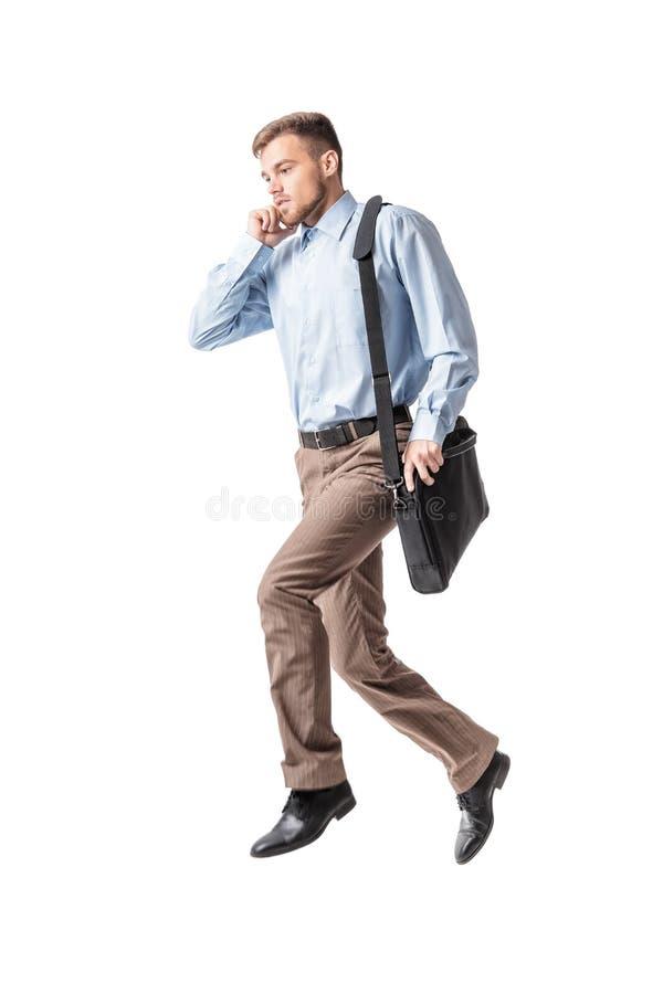 Hombre de negocios que se ejecuta y que habla por el teléfono fotografía de archivo libre de regalías