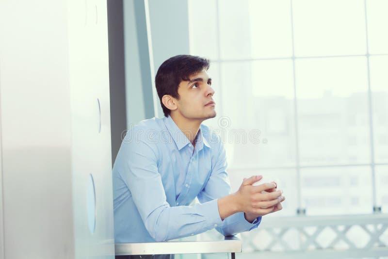 Hombre de negocios que se inclina en las verjas del balcón fotos de archivo