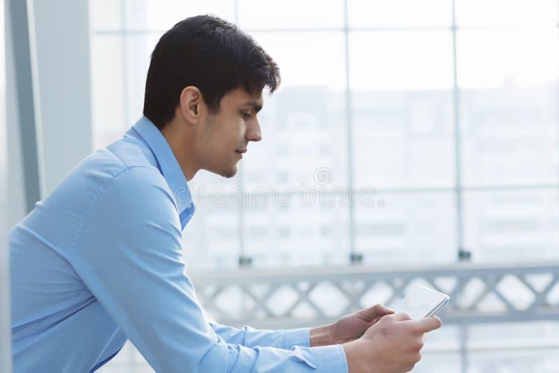 Hombre de negocios que se inclina en las verjas del balcón foto de archivo libre de regalías