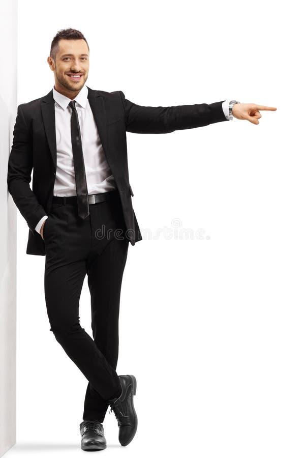 Hombre de negocios que se inclina en una pared y que señala al lado fotografía de archivo