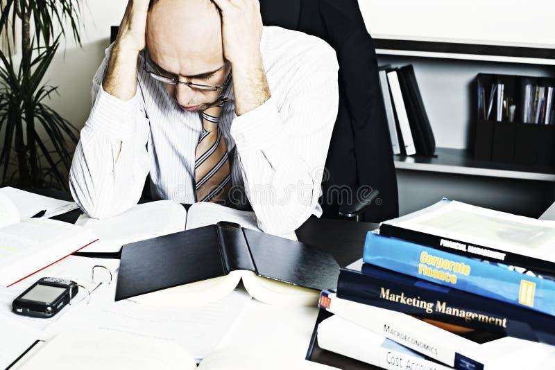 Hombre de negocios que se inclina sobre estudiar del escritorio de oficina foto de archivo