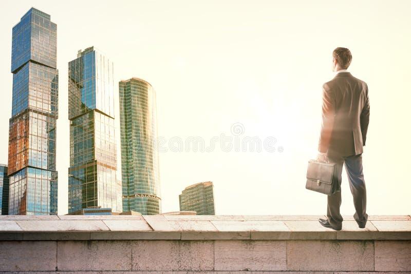 Hombre de negocios que se opone con la parte posterior a ciudad imagen de archivo libre de regalías