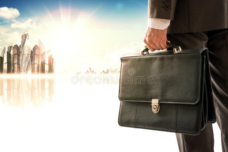 Hombre de negocios que se opone con la parte posterior a ciudad fotografía de archivo libre de regalías