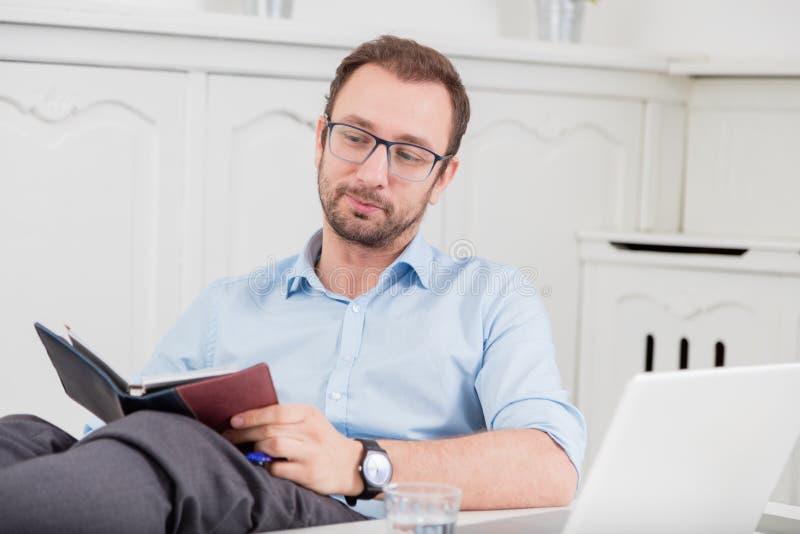 Hombre de negocios que se relaja con las piernas en su escritorio en la oficina imagenes de archivo
