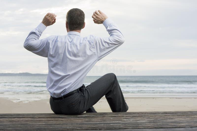 Hombre de negocios que se relaja en el mar fotografía de archivo libre de regalías