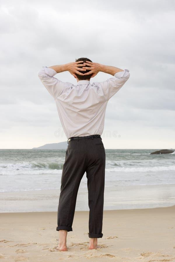 Hombre de negocios que se relaja en la playa fotografía de archivo