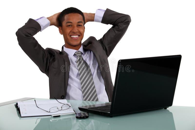 Hombre de negocios que se relaja en su escritorio imagenes de archivo