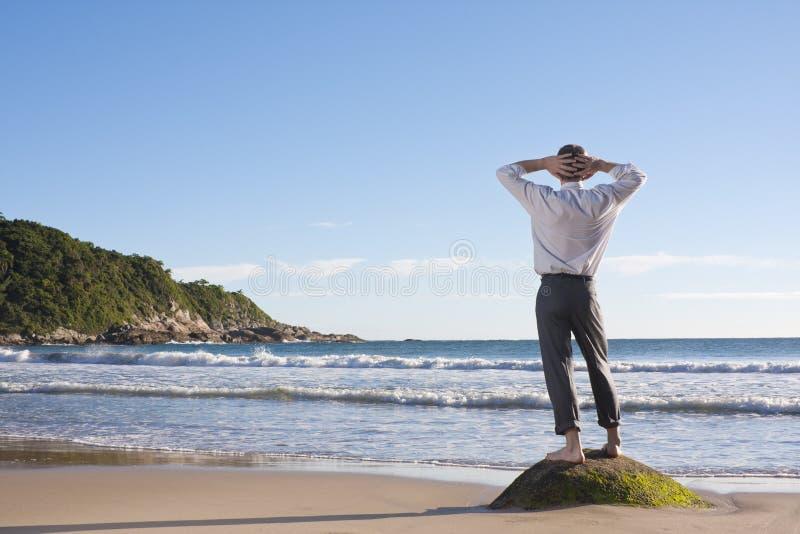 Hombre de negocios que se relaja en una playa fotografía de archivo