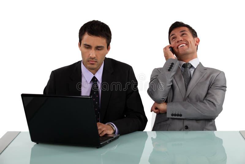 Hombre de negocios que se sienta al lado de colega fotografía de archivo libre de regalías