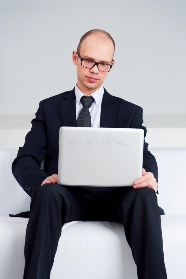Hombre de negocios que se sienta con el ordenador portátil imagenes de archivo
