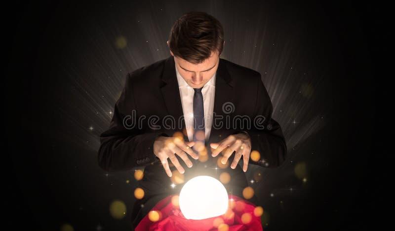 Hombre de negocios que se sienta con la bola mágica chispeante stock de ilustración