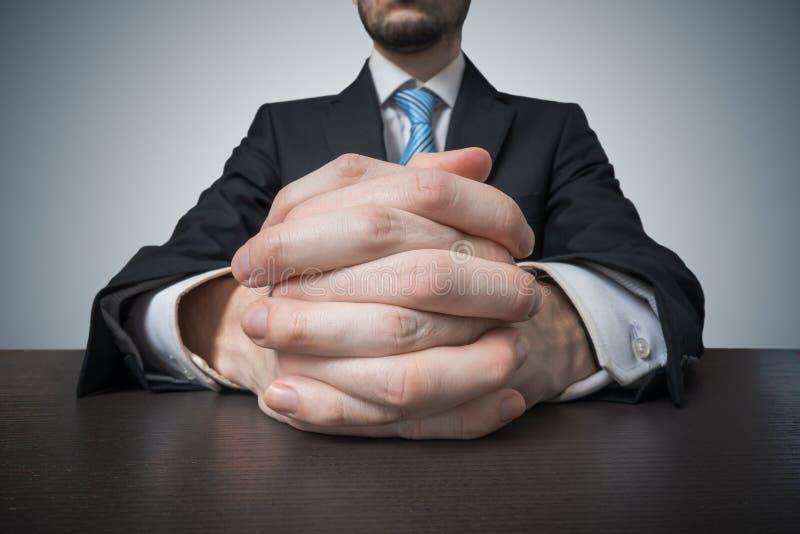 Hombre de negocios que se sienta con las manos abrochadas Negociación y concepto del tratamiento imágenes de archivo libres de regalías