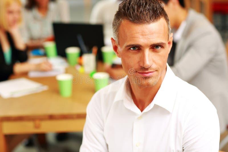 Hombre de negocios que se sienta delante de colegas fotos de archivo
