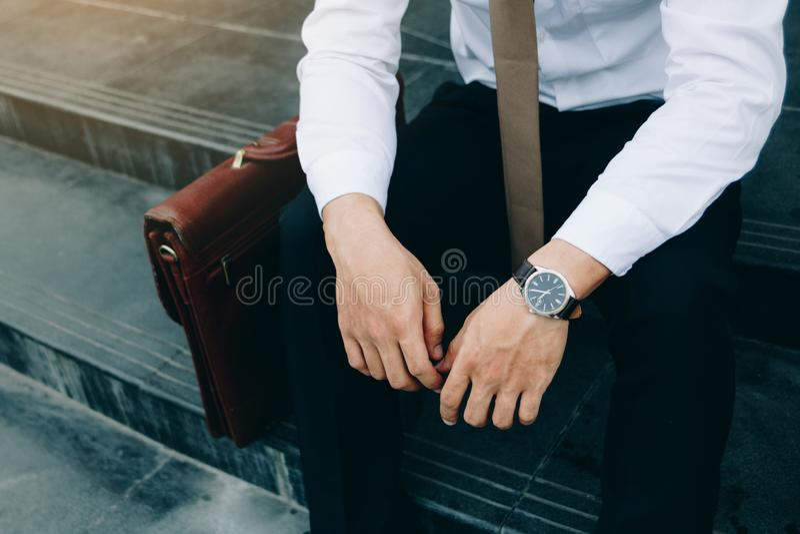 Hombre de negocios que se sienta delante del edificio de la compa??a con concepto de la esperanza fotografía de archivo