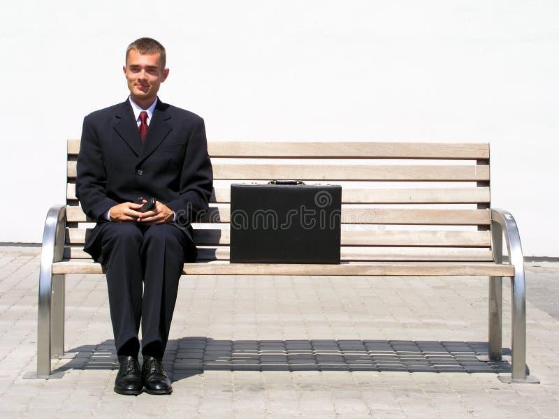 Hombre de negocios que se sienta en banco foto de archivo