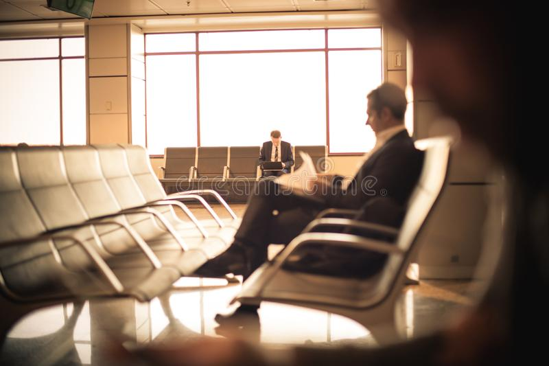 Hombre de negocios que se sienta en el aeropuerto, esperando su vuelo fotografía de archivo libre de regalías