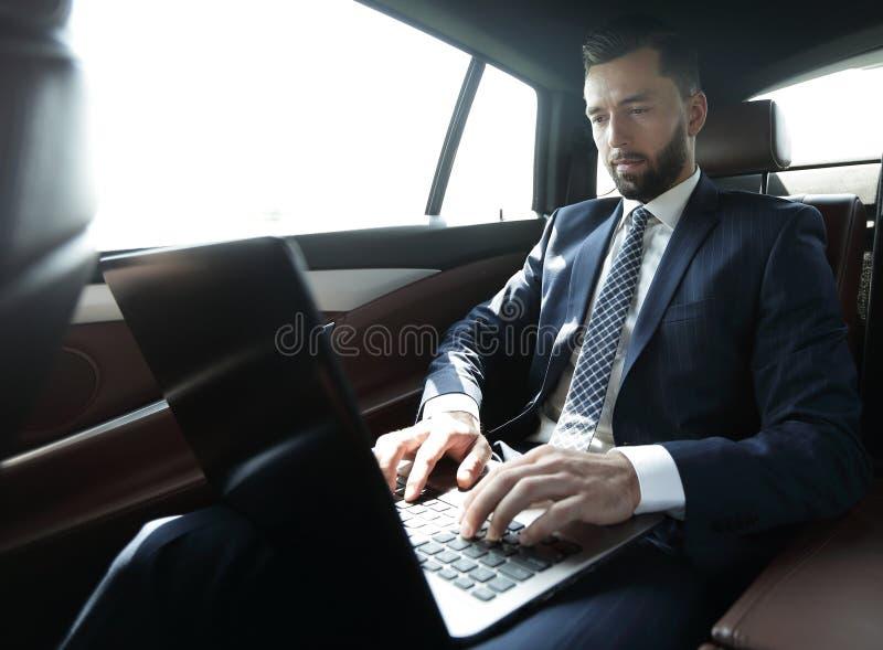 Hombre de negocios que se sienta en el asiento de atrás de un coche, usando su ordenador portátil foto de archivo