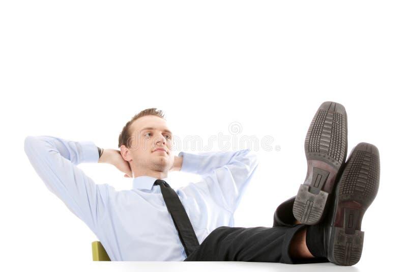 Hombre de negocios que se sienta en el escritorio foto de archivo