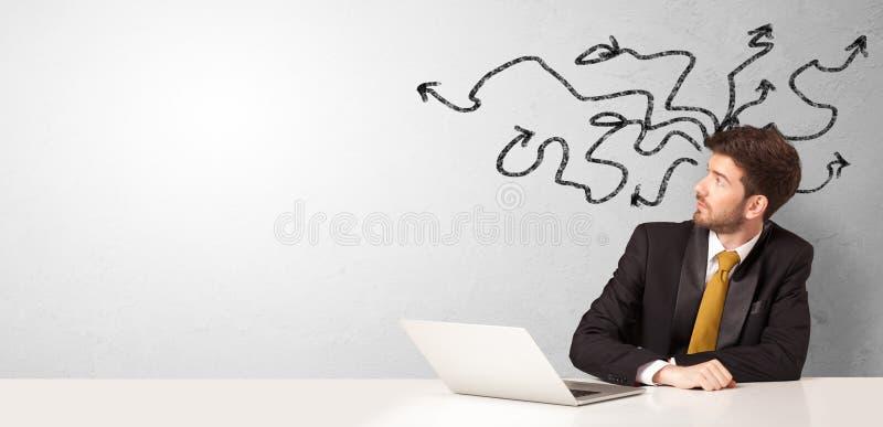 Hombre de negocios que se sienta en el escritorio con las flechas alrededor imágenes de archivo libres de regalías
