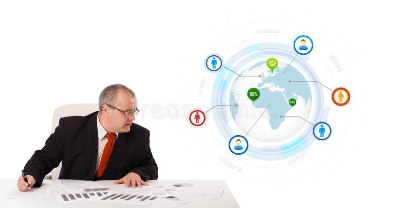 Hombre de negocios que se sienta en el escritorio con un globo foto de archivo libre de regalías