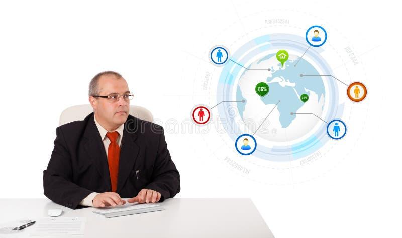 Hombre de negocios que se sienta en el escritorio y que mecanografía en el teclado con el globo fotografía de archivo