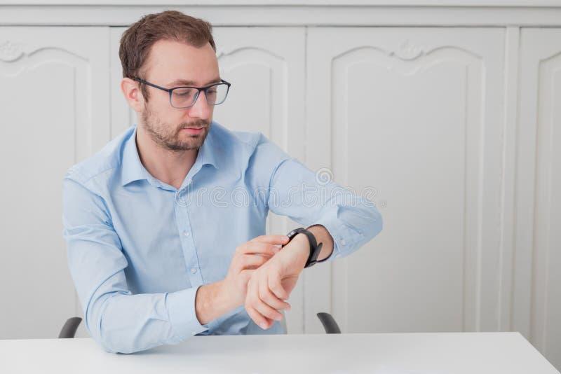 Hombre de negocios que se sienta en el escritorio y que mira en su reloj fotografía de archivo