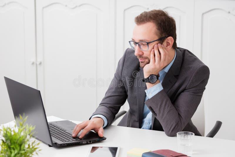 Hombre de negocios que se sienta en el escritorio y que mira la pantalla del ordenador portátil imágenes de archivo libres de regalías