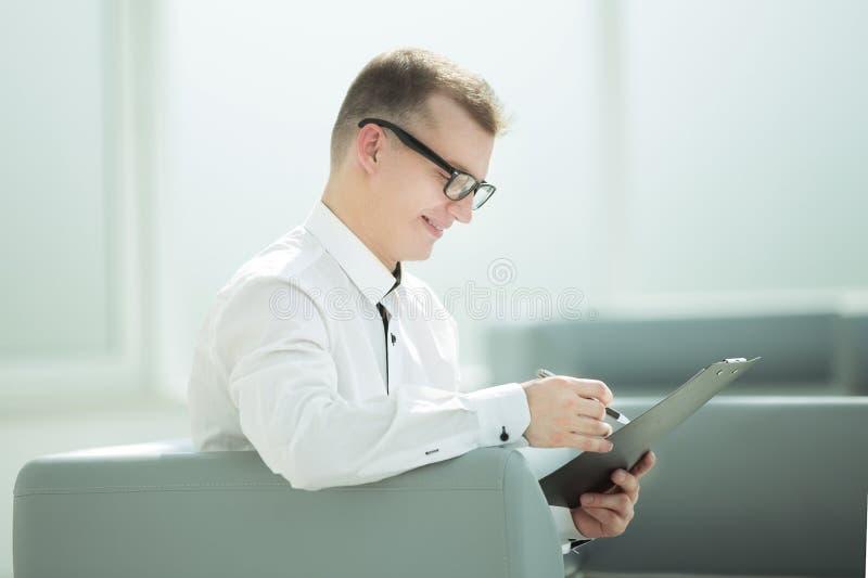 Hombre de negocios que se sienta en el pasillo de la oficina y que lee un documento de negocio imagen de archivo