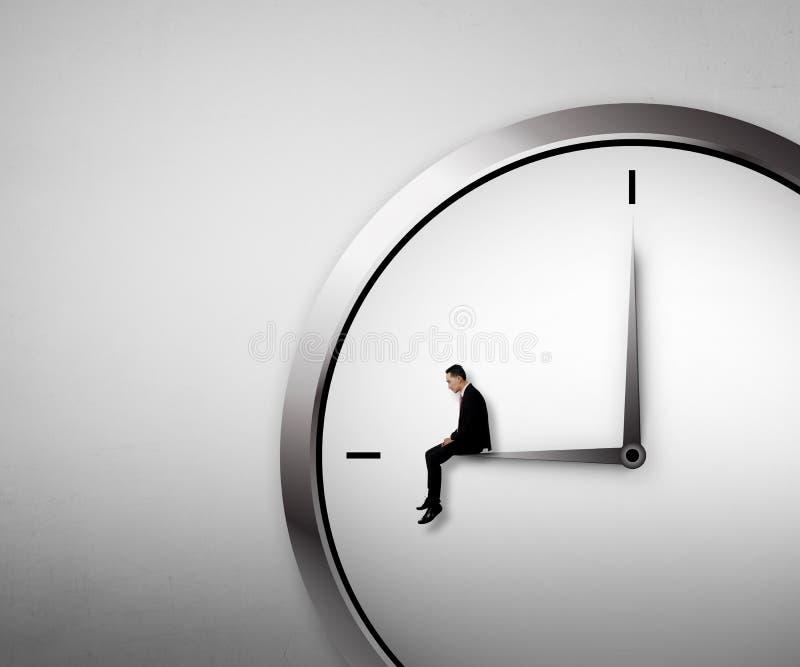 Hombre de negocios que se sienta en el reloj imagen de archivo