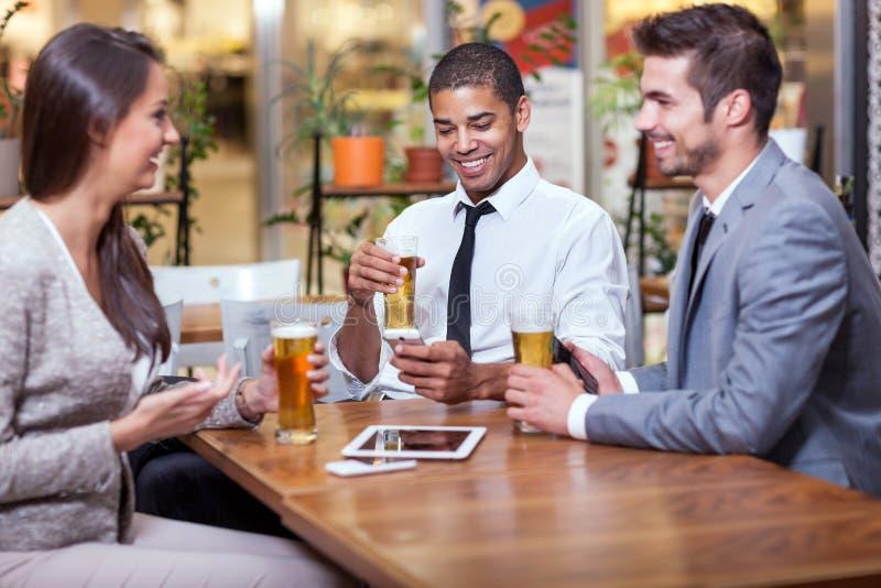 Hombre de negocios que se sienta en el restaurante y que celebra éxito con imagen de archivo