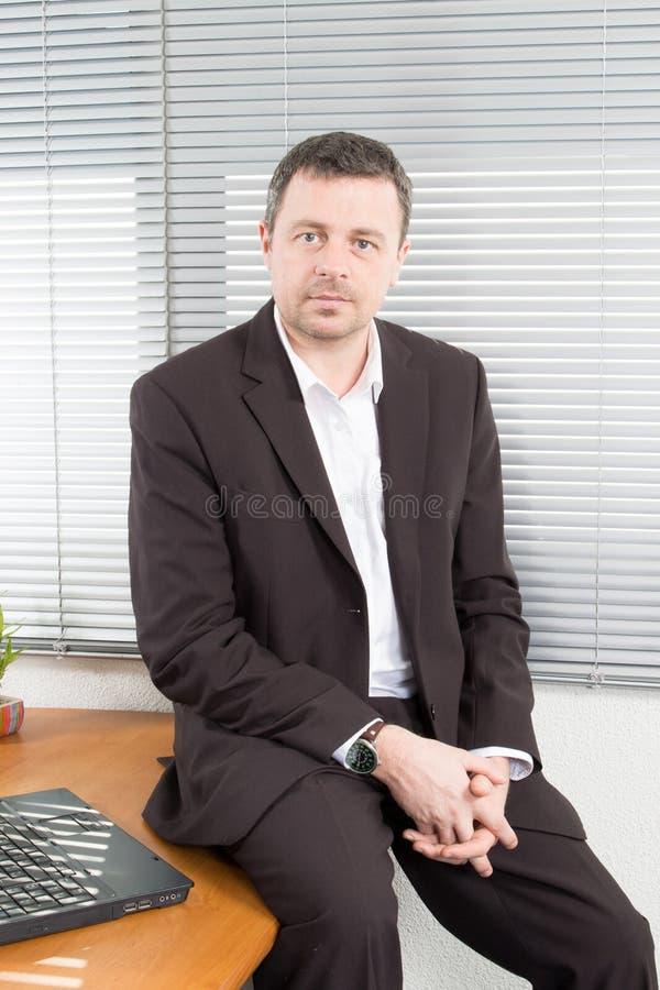 hombre de negocios que se sienta en el retrato de la oficina del escritorio del hombre de negocios que mira la cámara fotos de archivo