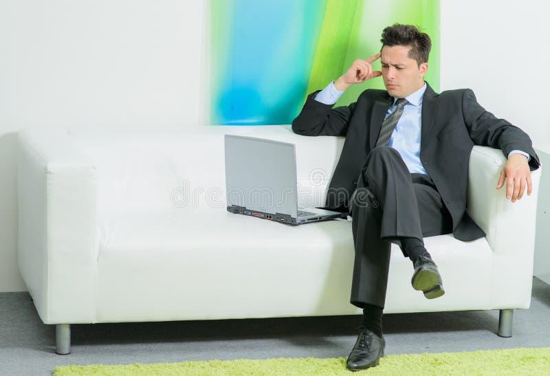 Hombre de negocios que se sienta en el sofá con el ordenador portátil imagen de archivo libre de regalías