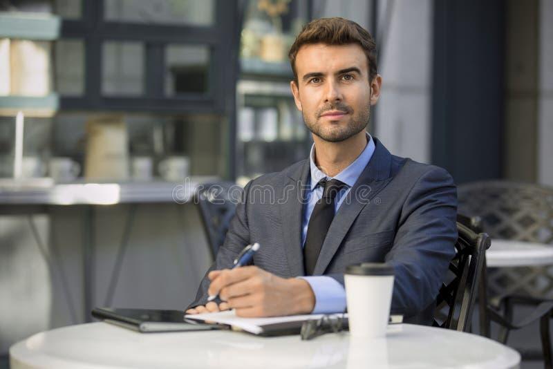 Hombre de negocios que se sienta en la cafetería con el retrato del papeleo fotografía de archivo