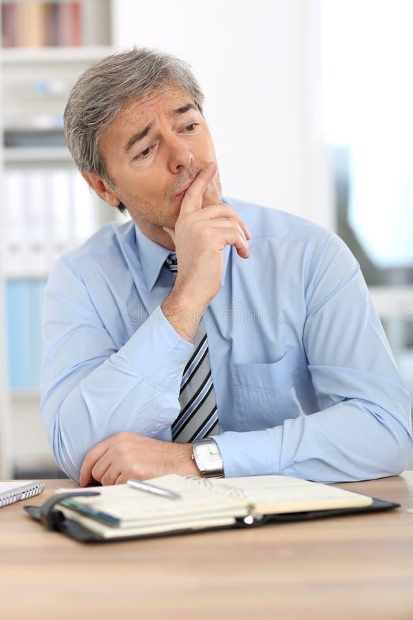 Hombre de negocios que se sienta en la oficina imagen de archivo