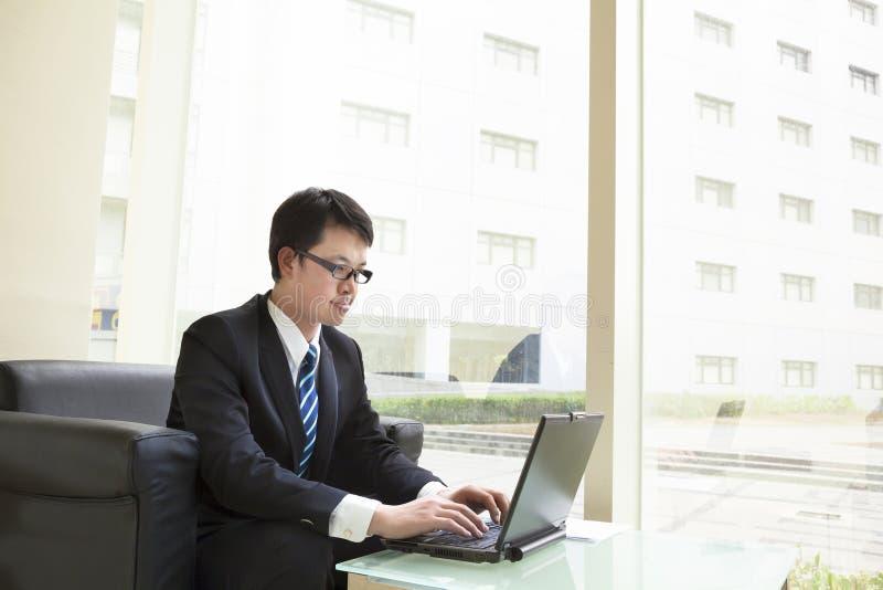 Hombre de negocios que se sienta en la oficina brillante que trabaja en el ordenador portátil fotos de archivo libres de regalías
