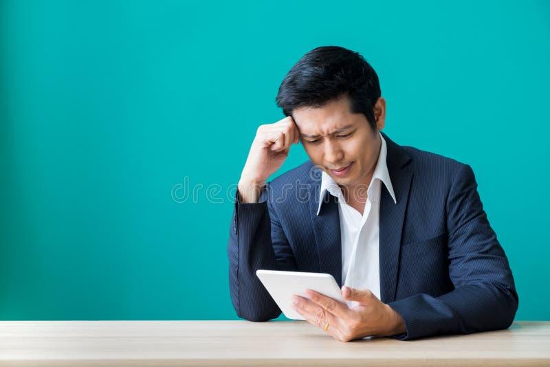 Hombre de negocios que se sienta en la tabla de madera y la pared verde y que mira el dow imagenes de archivo