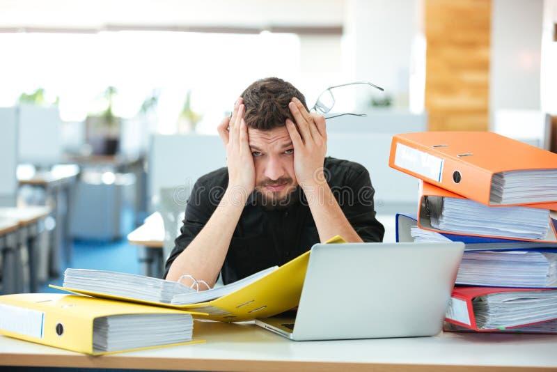 Hombre de negocios que se sienta en la tabla en oficina foto de archivo