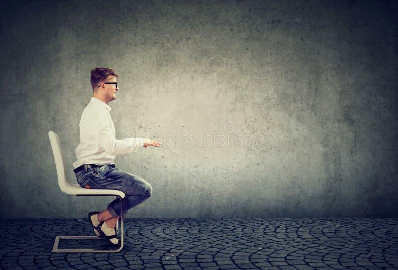 Hombre de negocios que se sienta en la tabla invisible que finge mecanografiar en el ordenador imagen de archivo libre de regalías