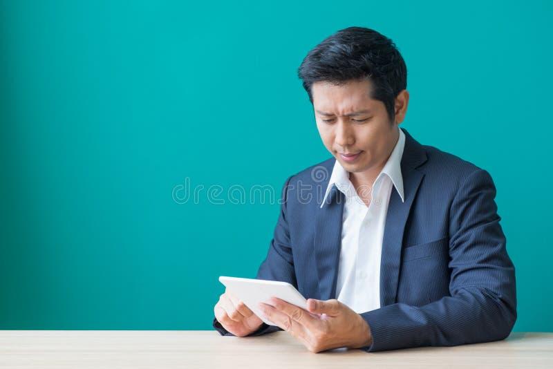Hombre de negocios que se sienta en la tabla de madera y la pared verde y que mira el dow imagen de archivo libre de regalías