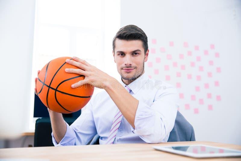 Hombre de negocios que se sienta en la tabla y que sostiene la bola fotos de archivo