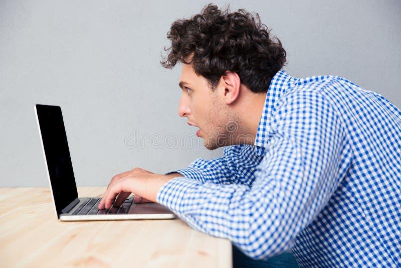 Hombre de negocios que se sienta en la tabla y que usa el ordenador portátil imagen de archivo