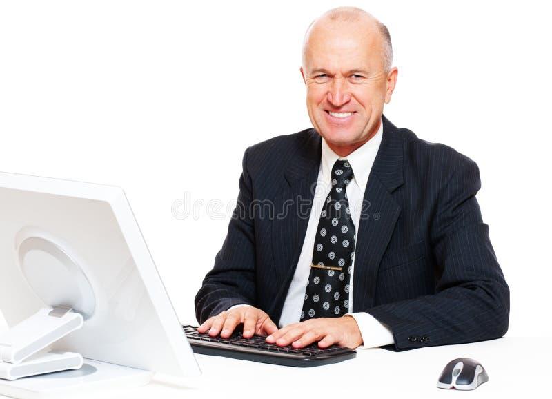 Hombre de negocios que se sienta en lugar de trabajo y la sonrisa imagenes de archivo