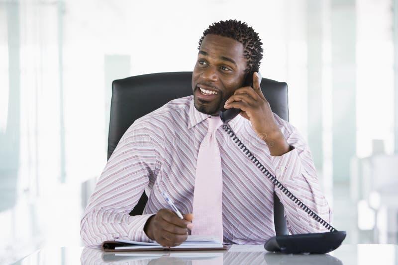 Hombre de negocios que se sienta en oficina con personal fotos de archivo