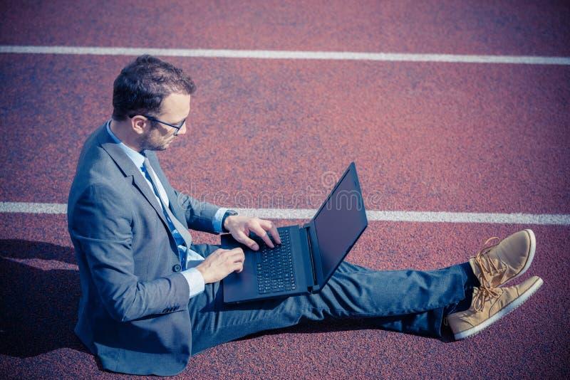 Hombre de negocios que se sienta en pista que compite con y que trabaja en el ordenador portátil fotografía de archivo libre de regalías
