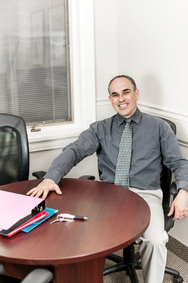 Hombre de negocios que se sienta en sala de reunión de la oficina foto de archivo