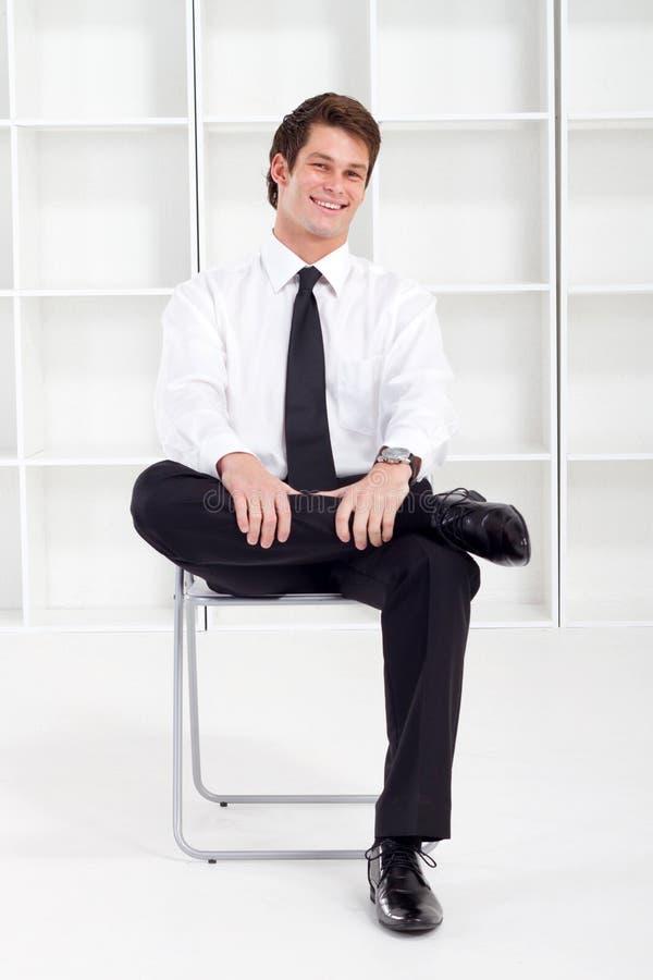 Hombre de negocios que se sienta en silla imagen de archivo