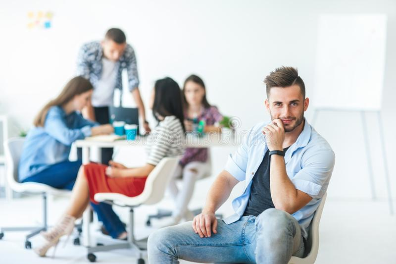 Hombre de negocios que se sienta en silla delante de su equipo del negocio foto de archivo