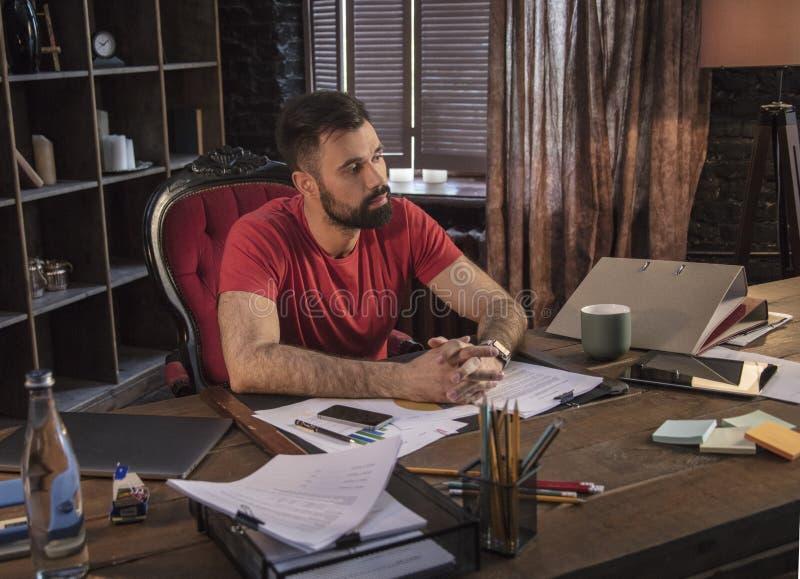 Hombre de negocios que se sienta en silla en la tabla de madera con smartphone y el ordenador portátil de la tableta fotografía de archivo