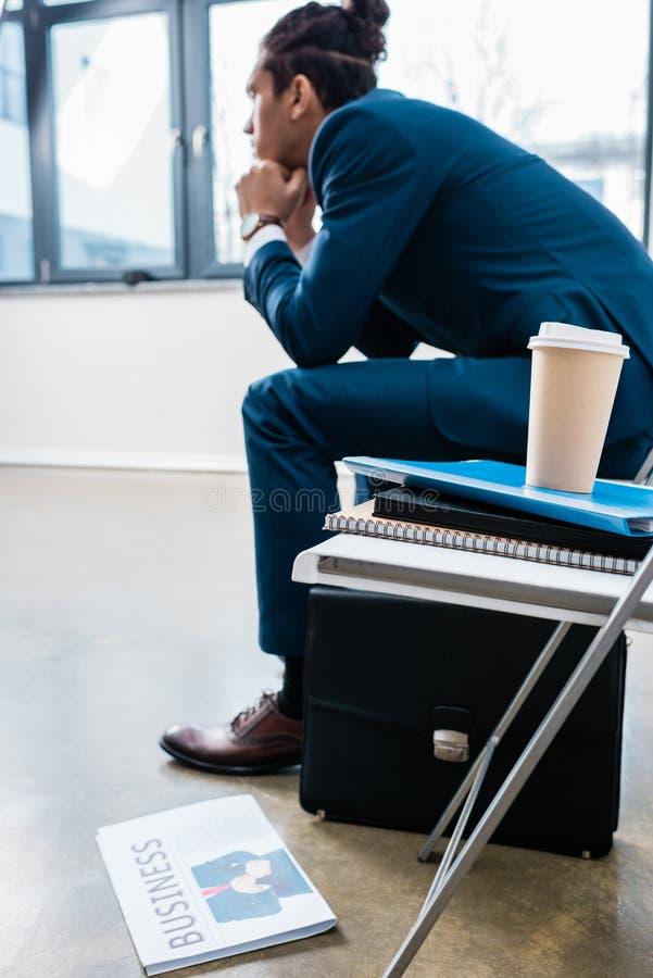 Hombre de negocios que se sienta en silla y que espera por la pila de documentos fotografía de archivo libre de regalías