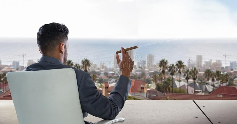 Hombre de negocios que se sienta en silla y que mira la ciudad mientras que fuma el cigarro imagenes de archivo